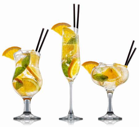 Vers fruit alcohol cocktail of mocktail in klassieke glazen met ijsblokjes, sinaasappel en mint geïsoleerd op een witte achtergrond