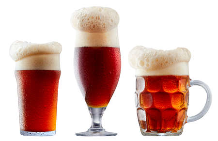 Mugs of frosty dark red beer with foam isolated on a white background