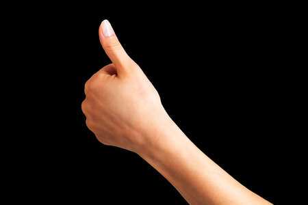 Woman holding hand in gesture of like sign, giving thumb up on black background. Isolated with clipping path.