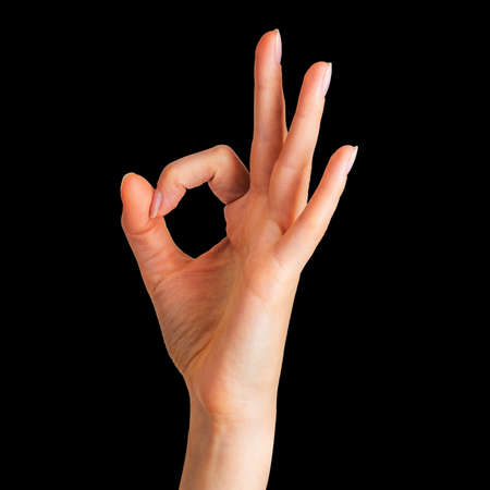 Woman holding hand in gesture of okay. Sign of success, victory or luck on black background. Isolated with clipping path.