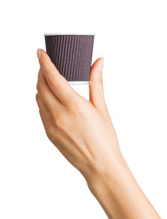 Main de femme tenant une tasse à café en papier avec capuchon jetable sur fond blanc. Isolé avec un tracé de détourage.