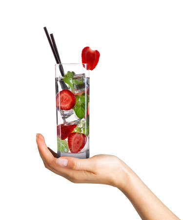 Woman hand holding cocktail in tall glass on white background.