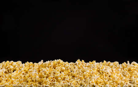 Scattered popcorn isolated on black background, concept of watching TV or cinema.