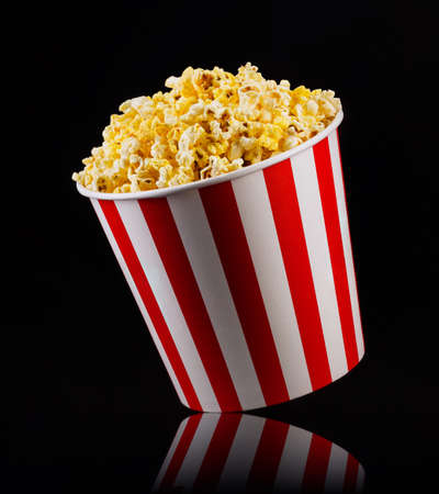 Paper striped bucket with popcorn isolated on black