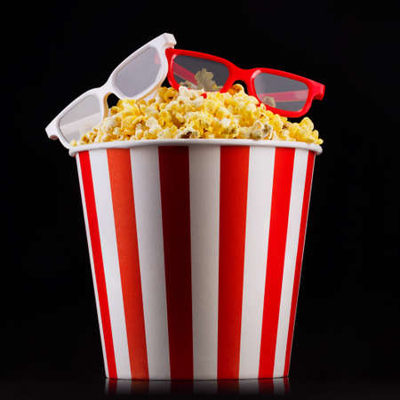 Paper striped bucket with popcorn and glasses isolated on black Banco de Imagens