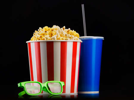 Paper striped bucket with popcorn, cup of soft and glasses isolated on black Banco de Imagens