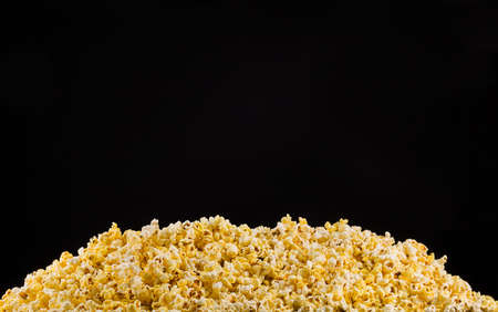 Scattered popcorn isolated on black Фото со стока