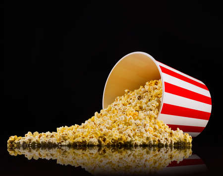 Scattered popcorn from paper striped bucket isolated on black Фото со стока