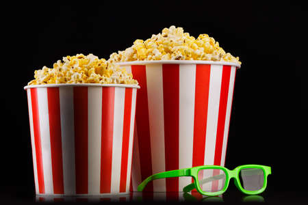 Paper striped buckets with popcorn and glasses isolated on black