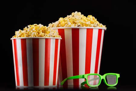 Papiergestreifte Eimer mit Popcorn und Gläsern isoliert auf Schwarz