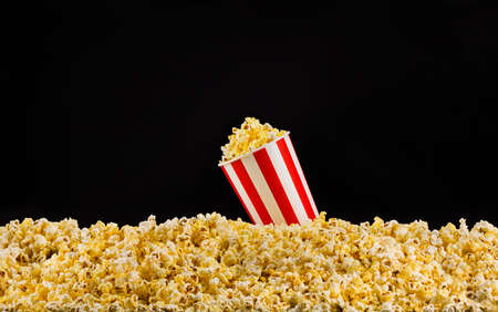 Paper striped bucket installed on scattered popcorn isolated on black