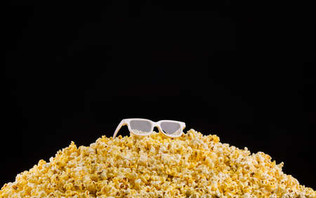 Cinema glasses installed on scattered popcorn isolated on black