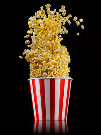 Flying popcorn from paper striped bucket isolated on black