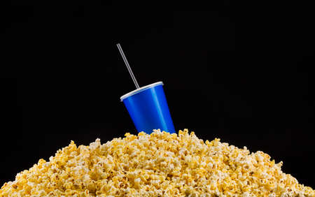 Blue cup with cap and tube installed on scattered popcorn isolated on black Banco de Imagens
