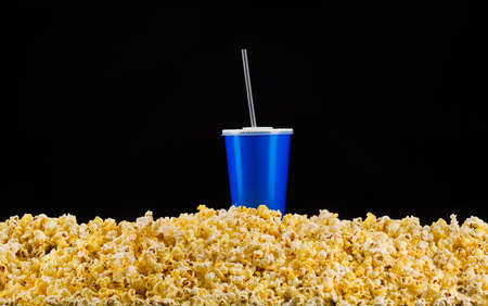 Blue cup with cap and tube installed on scattered popcorn isolated on black 写真素材