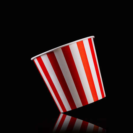 Empty popcorn striped bucket isolated on black Banco de Imagens