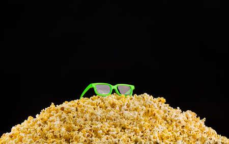 Cinema glasses installed on scattered popcorn isolated on black