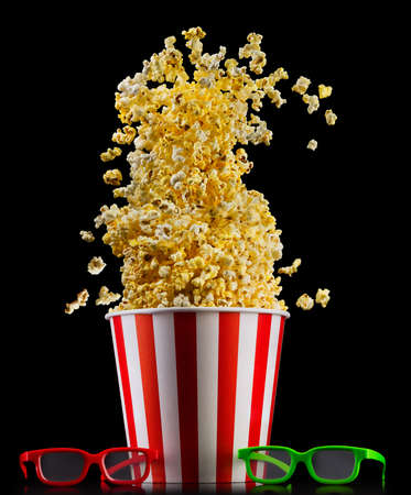 Paper striped bucket with popcorn and glasses isolated on black background, movie night concepto or watching TV.