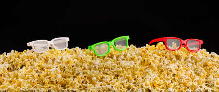 Cinema glasses installed on scattered popcorn isolated on black background, concept of watching TV or cinema.
