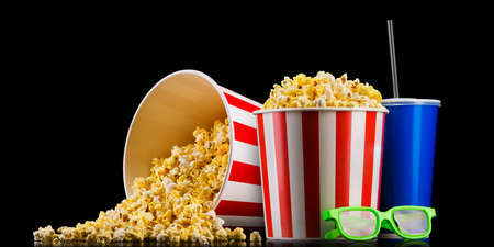 Paper striped bucket with popcorn, cup of soft and glasses isolated on black Imagens