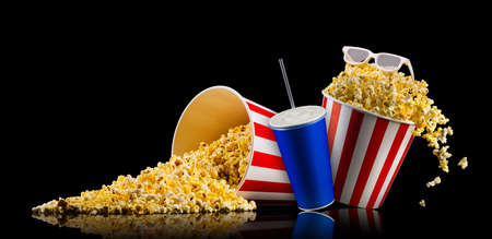 Set of paper striped bucket with popcorn and cup of soft drink isolated on black