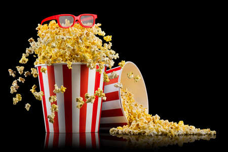 Set of bucket with popcorn and 3D glasses isolated on black background, concept of watching TV or cinema. 版權商用圖片
