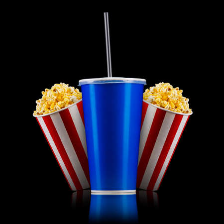Paper striped bucket with popcorn and cup of soft drink isolated on black background, movie night concepto or watching TV.