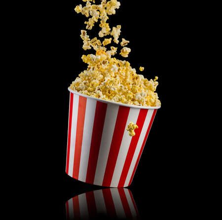 Flying popcorn from paper striped bucket isolated on black background, concept of watching TV or cinema.