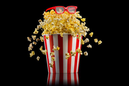 Flying popcorn from paper striped bucket with 3D glasses isolated on black background, concept of watching TV or cinema.