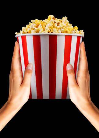 Woman hand holding paper striped bucket with popcorn isolated on black