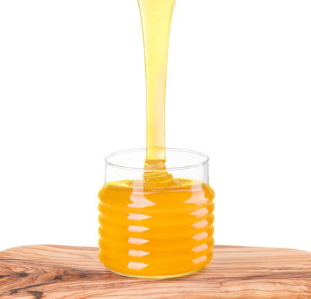 Glass jar full of honey and falling jet of honey on wooden plank isolated on white with clipping path. Bee products by organic natural ingredients concept