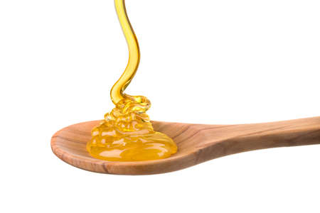 Falling and flowing honey on a wooden spoon isolated on white background with clipping path.
