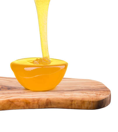 Glass bowl full of honey and falling jet of honey on wooden plank isolated on white background with clipping path. Bee products by organic natural ingredients concept Reklamní fotografie