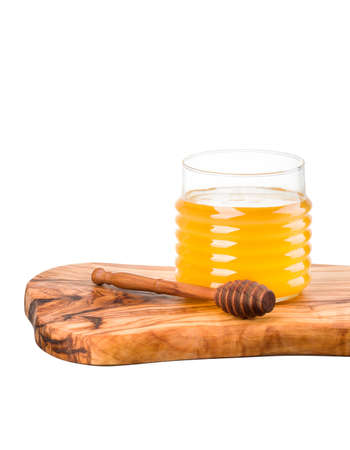 Glass jar full of honey and wooden dipper on wooden plank isolated on white background with clipping path Reklamní fotografie