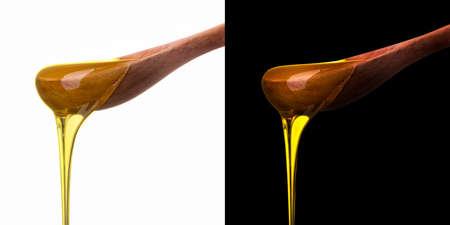 Ensemble de cuillère en bois avec du miel tombant isolé sur blanc et noir