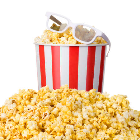Paper striped bucket and 3D glasses on a heap of popcorn isolated on white