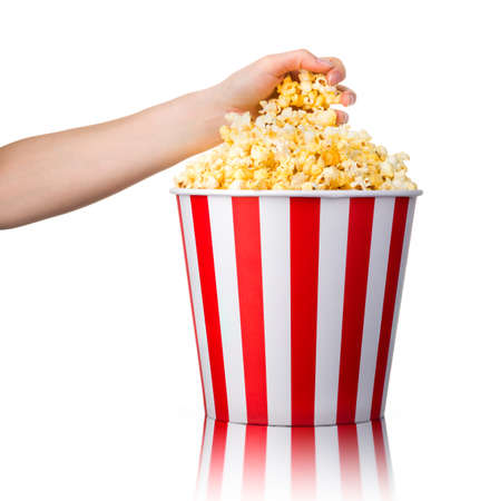 Woman hand picking popcorn from striped bucket isolated on white