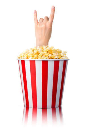 Female hand sticks out of a bucket with popcorn showing rock n roll sign or giving the devil horns gesture isolated on white