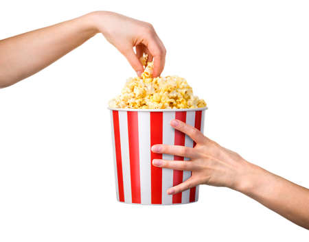 Woman hand taking popcorn from striped bucket isolated on white