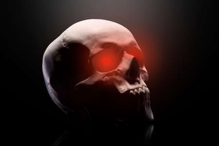 Model of the human skull with red eyes isolated on black