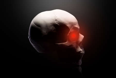 Model of the human skull with red eyes isolated on black 免版税图像