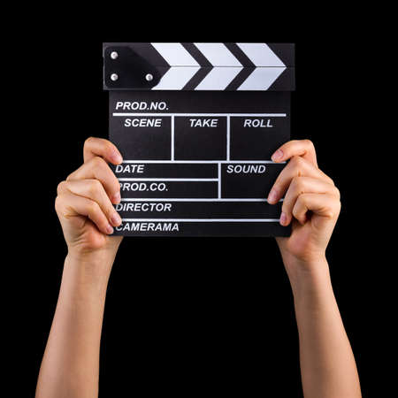 Human hand holding film clapper board isolated on black