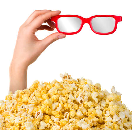 Female hand sticks out of a pile of popcorn showing 3D glasses isolated on white background. Isolated with clipping path.