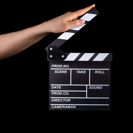 Human hand holding fiilm clapper board isolated on black background with clipping path.