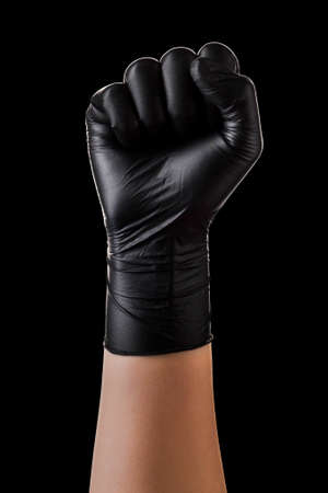 Hand in black gloves taking or showing something on black background.