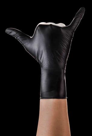 Hand in black gloves showing Shaka or surfer sign on black background.