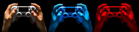 Set of hands holding video game gamepad in neon lights isolated on a black background, concept of playing games or watching TV.