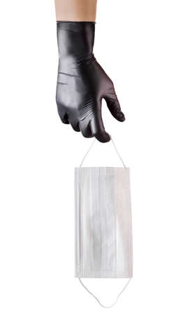 Hand in black gloves hold disposable face mask isolated on white background . Concept of medical and healthcare 版權商用圖片