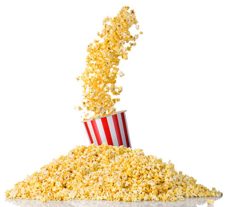 Flying popcorn from paper striped bucket and scattered popcorn isolated on white background. Concept of cinema or watching TV. 版權商用圖片
