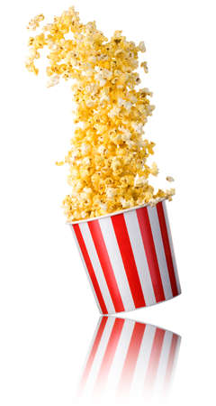 Flying popcorn from paper striped bucket isolated on white background  . Concept of cinema or watching TV. 版權商用圖片